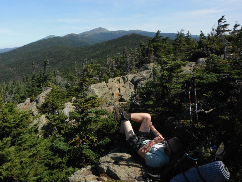 A thru-hiker relaxing, with Mount Washington in view